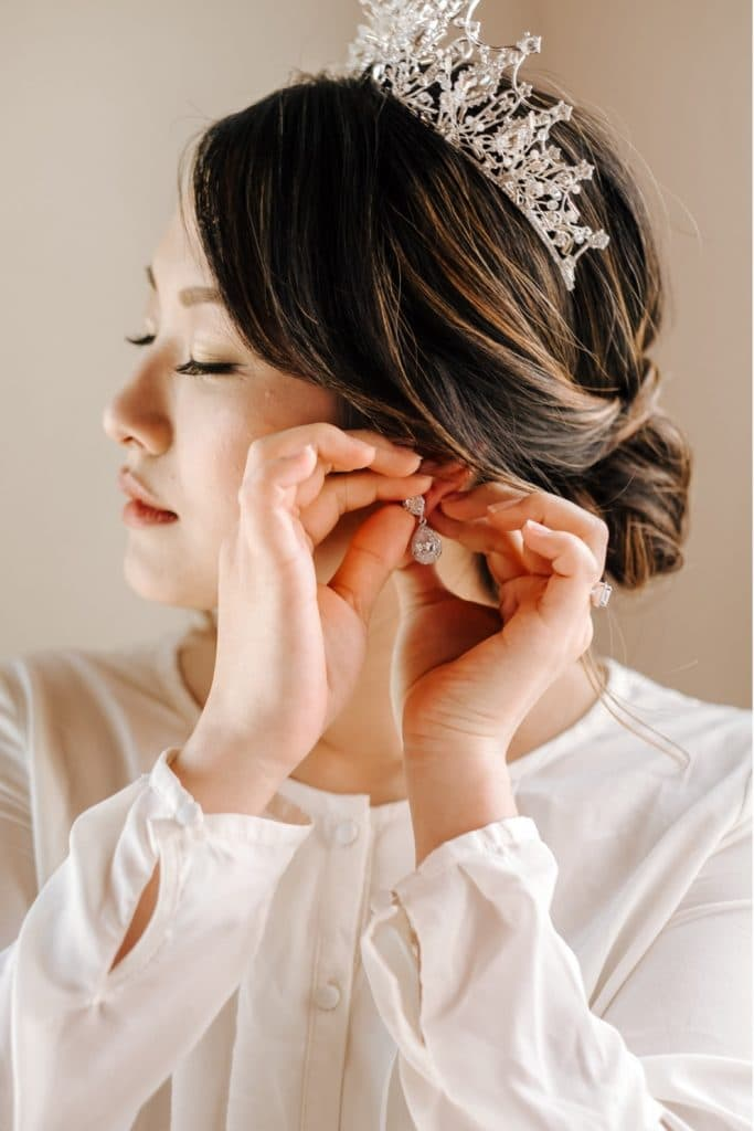 woman in pearl crown fastening large diamond earrings