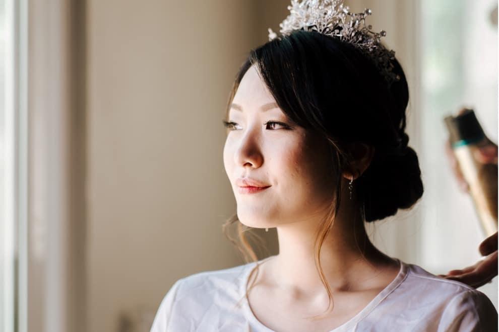 bride wearing pearl crown having her hair done