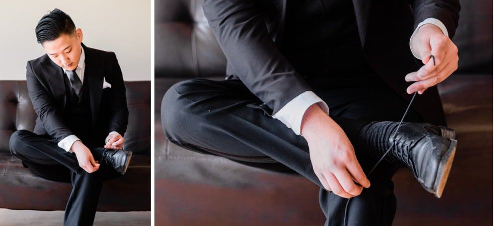 man in black suit lacing up leather dress shoes