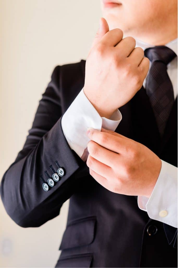 man in black suit buttoning up shirt sleeves