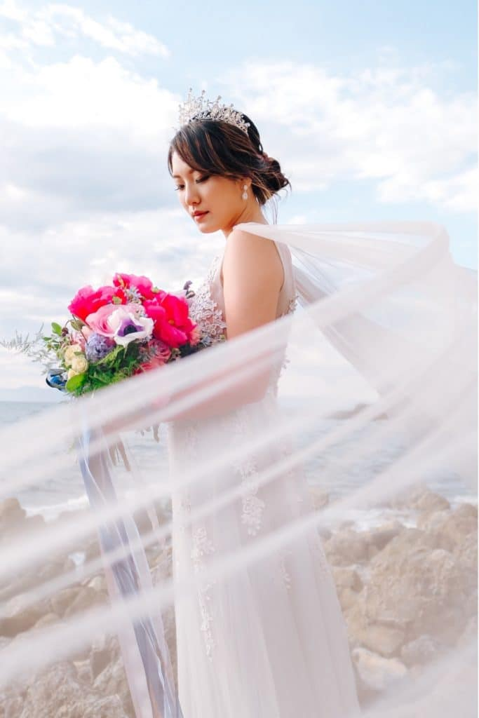 bride in purple gown and pearl crown holds colorful bouquet overlooking the ocean as veil blows in wind