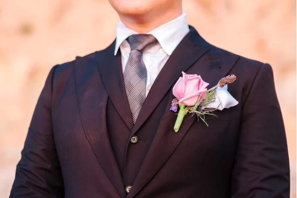 man in 3 piece black suit with colorful boutonniere