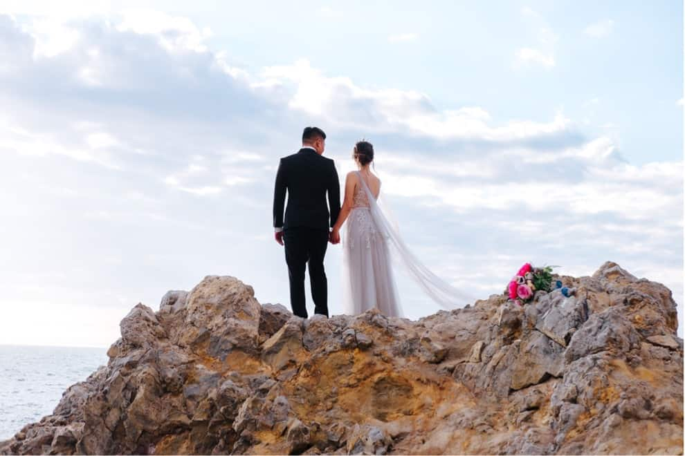 bride and groom stand on rocky outcropping overlooking ocean