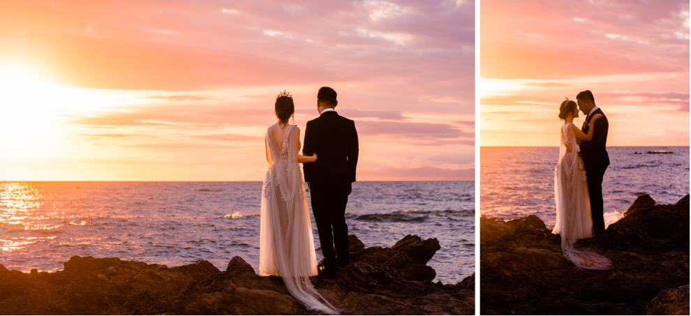 bride and groom stand on rocky outcropping overlooking ocean and colorful sunset