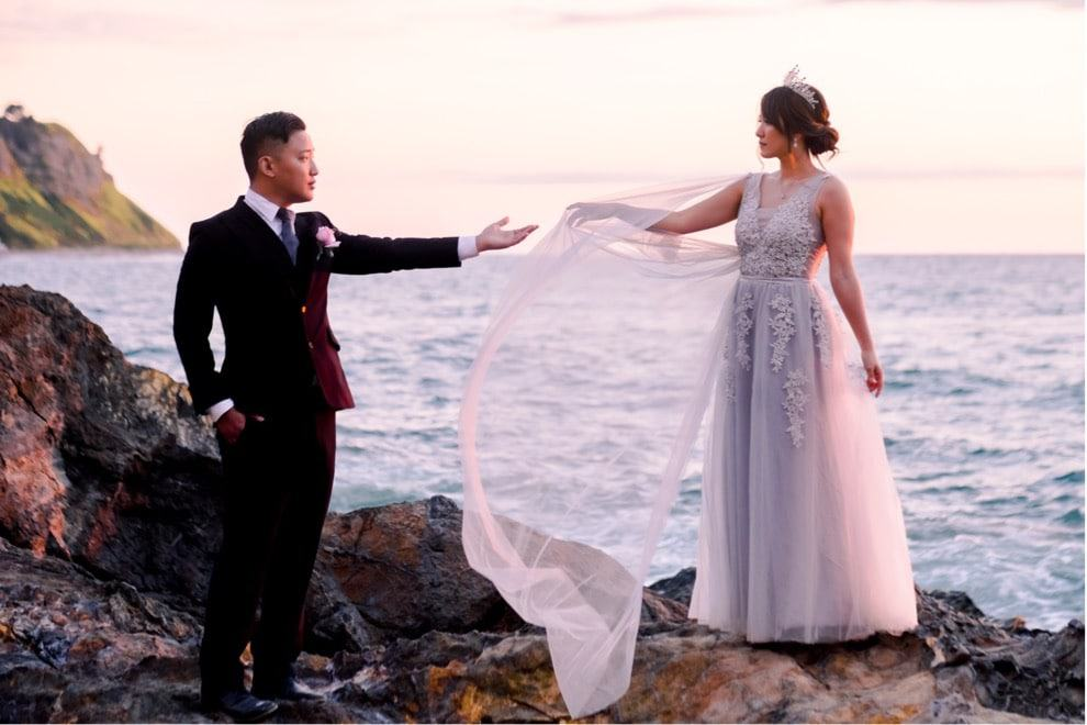 bride and groom reach for each other on rocky outcropping overlooking ocean and colorful sunset