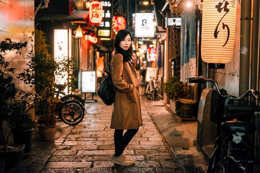 young woman standing in dimly lit alleyway at night