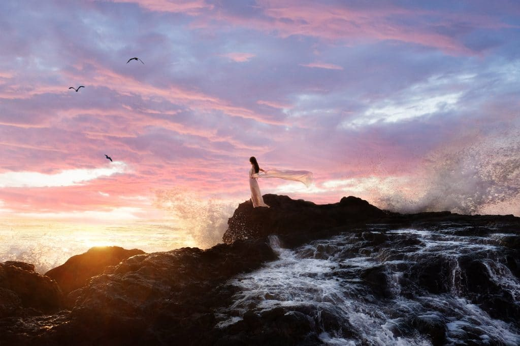 young woman standing on rocks as waves from ocean crash around her