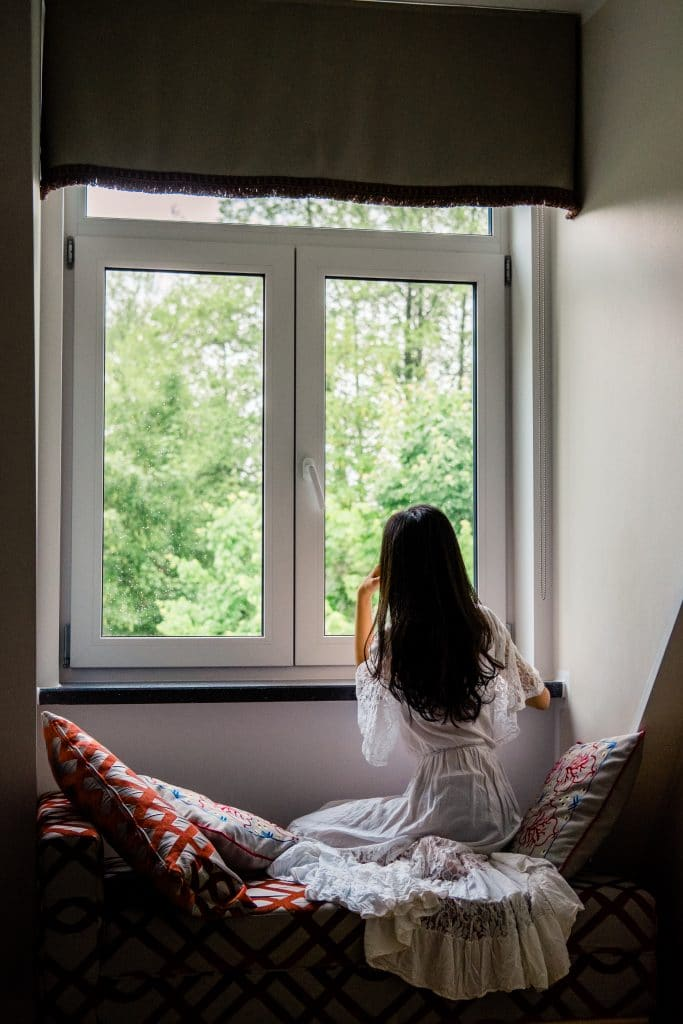young woman with long hair looks out a window