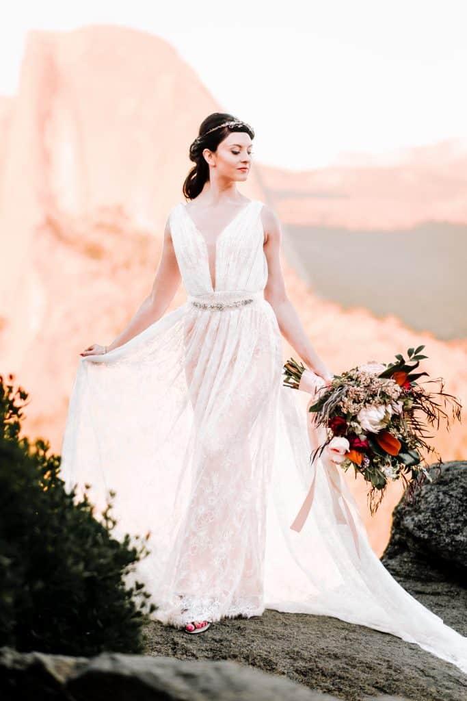 bride holding bouquet walking through Yosemite National Park