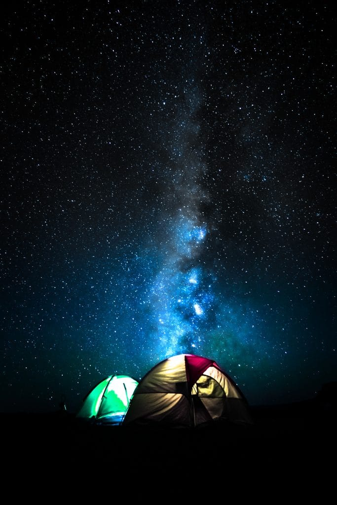 a beautiful starry sky with light from a camping tent below